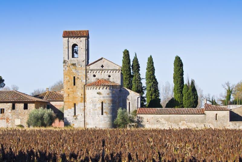 Chiesa romanica italiana antica tipica immersa nella campagna della Toscana vicino ad un cimitero fotografia stock libera da diritti