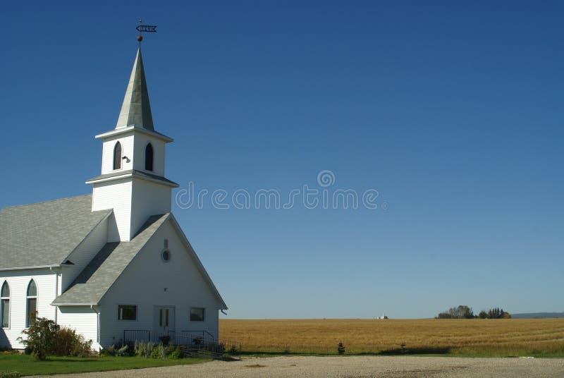 Chiesa rurale vicino al campo del coltivatore fotografie stock libere da diritti