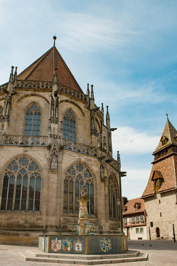Chiesa in Schwaebisch Gmuend, Germania con la fontana con la colonna di vergine Maria con l'aureola e bambino Gesù nella parte an fotografia stock
