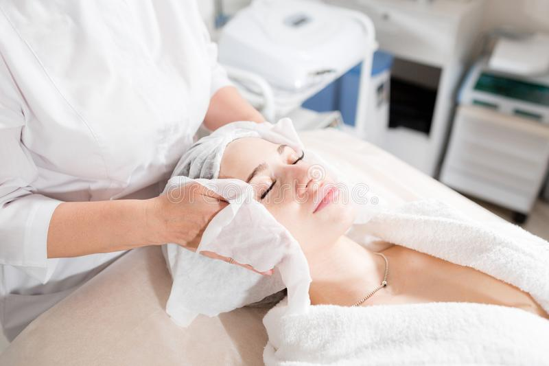 Chiffon avec le visage stérile de serviette Jeune jolie femme recevant des traitements dans des salons de beauté Mousse de nettoy photo libre de droits