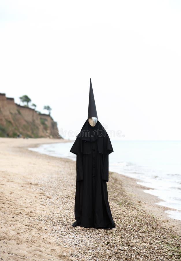 Chiffre étrange dans le manteau noir avec le visage de miroir en bord de la mer images libres de droits