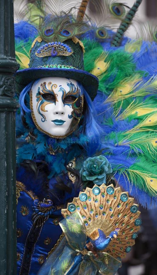 Chiffre de carnaval de Venise dans un costume coloré et un masque bleus, verts et jaunes Venise Italie image stock