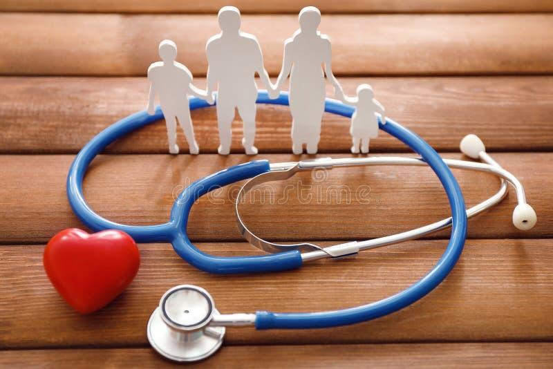Chiffre de famille, coeur rouge et stéthoscope sur le fond en bois Concept de soins de sant? photographie stock libre de droits