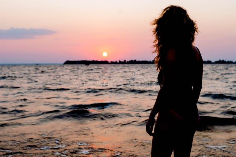 Chiffre de femme dans le maillot de bain regardant le lever de soleil stupéfiant près de la mer sur la plage image libre de droits