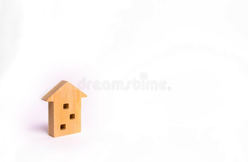 Chiffre en bois d'une maison à plusiers étages sur un fond blanc Maison à trois étages Achetant et se vendant des immobiliers, co photographie stock