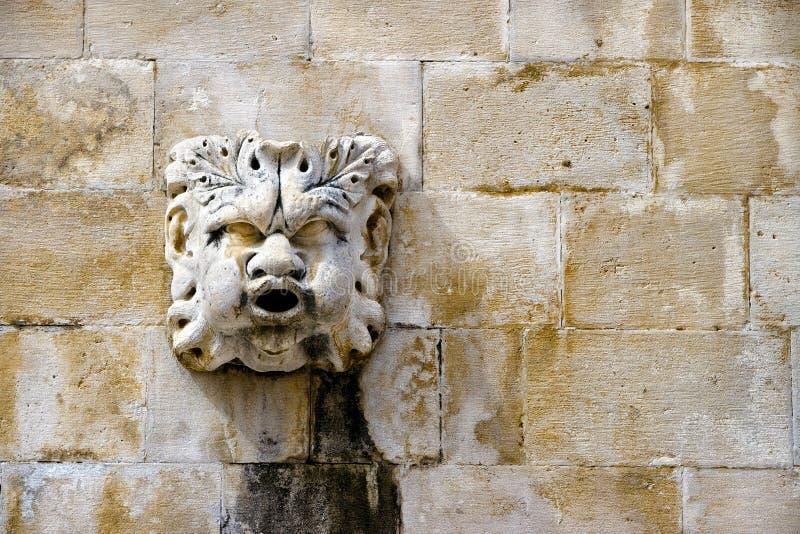 Chiffre en pierre de masque sur la fontaine antique, détail architectural d'o photographie stock