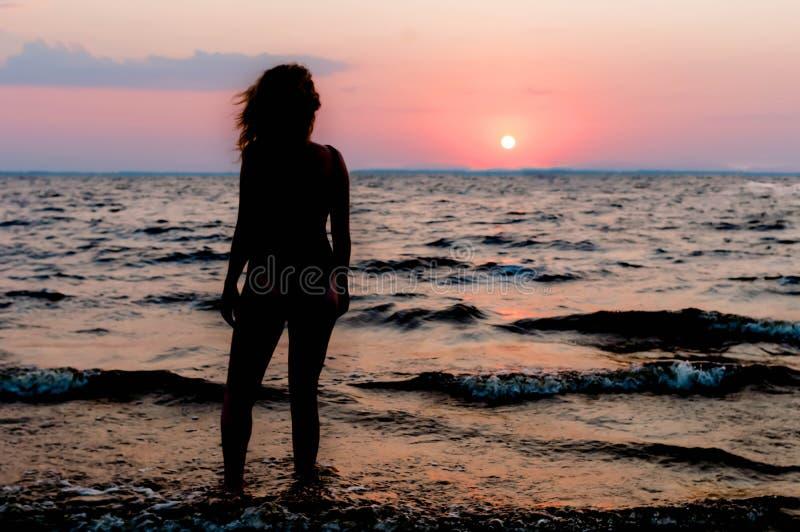 Chiffre mince de femme dans le maillot de bain tenant et regardant le lever de soleil stupéfiant photographie stock libre de droits