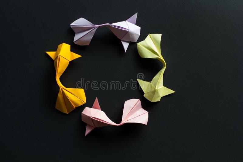 Chiffre ovale de cadre de cercle des poissons faits main de carpe de koi d'or d'origami de métier de papier sur le fond noir Vue  photos libres de droits