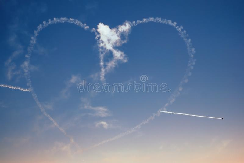 Chiffre plat acrobatique aérien de coeur de dessin d'avions dans le ciel photo libre de droits