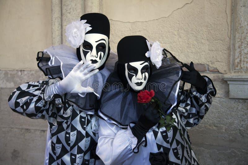 2 chiffres de carnaval de Venise dans des costumes noirs et blancs et masques sous l'arcade du palais Venise Italie du ` s de dog photographie stock