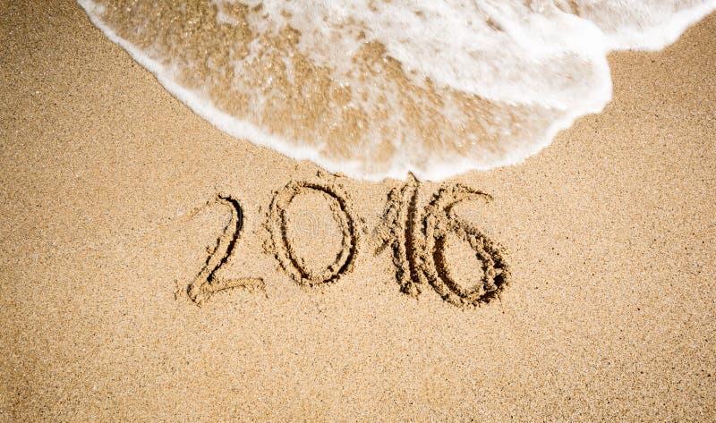Chiffres de la nouvelle année 2016 écrits sur le bord de la mer et étant enlevés photographie stock libre de droits