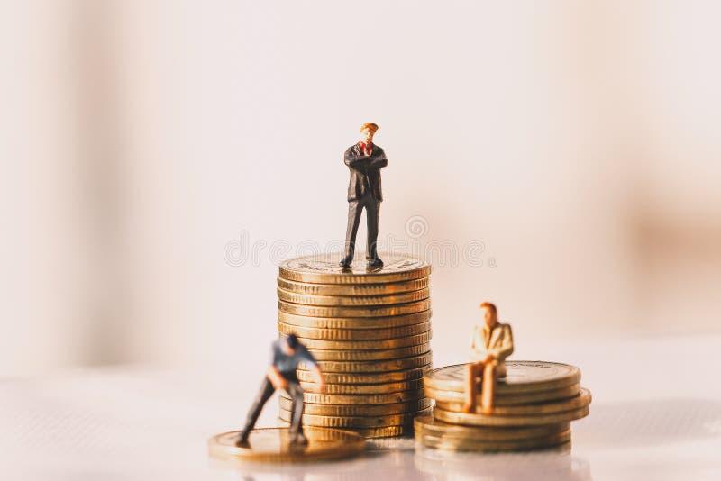 Chiffres de petit homme d'affaires se tenant et économie d'argent Concept d'investissement image libre de droits
