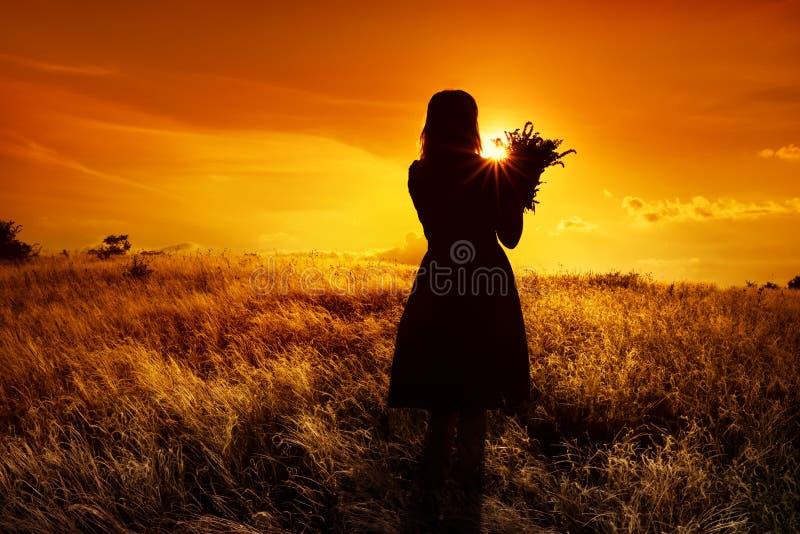 Chiffres de silhouette d'une fille avec un bouquet dans le domaine avec l'herbe pelucheuse au coucher du soleil Photo foncée au c image libre de droits