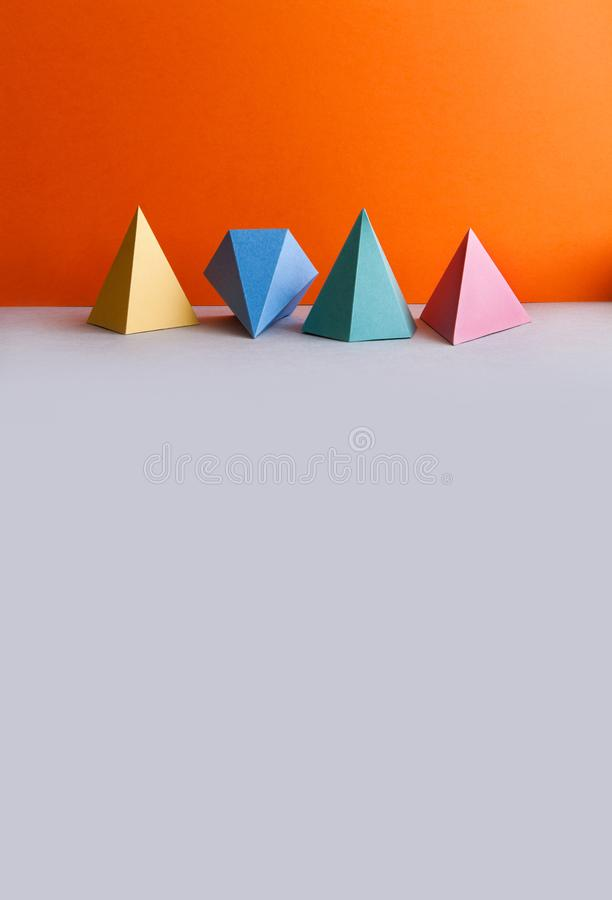 Chiffres géométriques solides platoniques La triangle rectangulaire de pyramide tridimensionnelle objecte sur le fond gris orange photos libres de droits