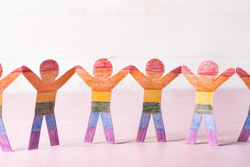 Chiffres humains de papier d'arc-en-ciel sur la table de couleur Concept de LGBT photos stock