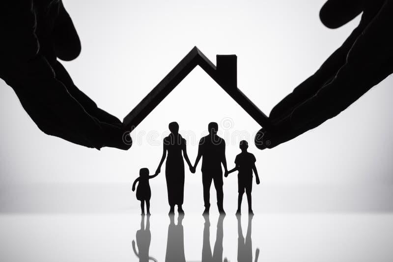 Chiffres protecteurs de famille de personne avec le toit photographie stock libre de droits