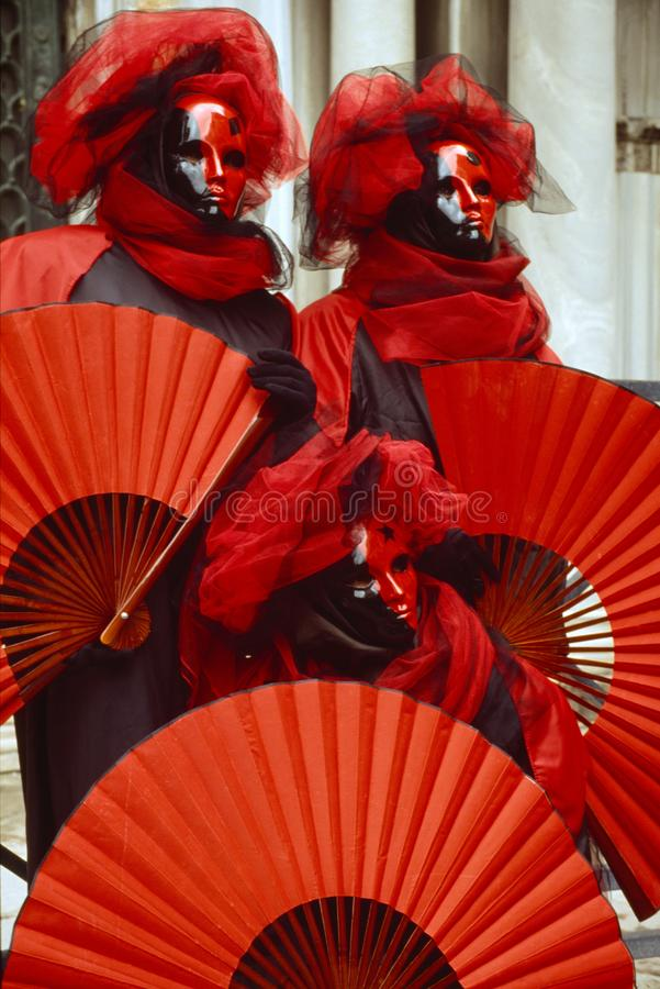 3 chiffres vénitiens de carnaval dans des costumes colorés et des masques rouges et noirs Venise Italie images libres de droits