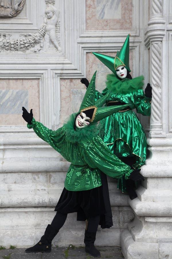 2 chiffres vénitiens de carnaval dans des costumes colorés et des masques verts et noirs Venise Italie images stock