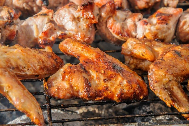 Chiken-Flügel und saftige gebratene Kebabs und auf dem BBQ stockfotografie