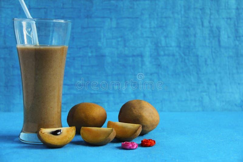 Chikoo或sapota用在浅兰的背景隔绝的它的汁液 库存照片