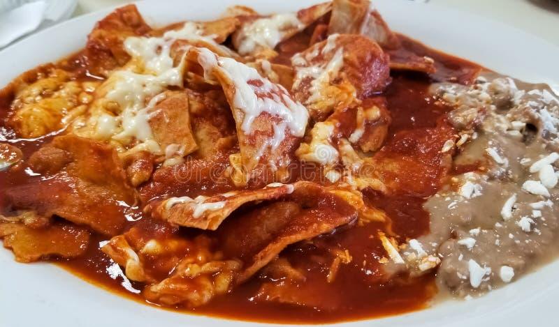 Chilaquiles, comida mexicana con las habas, el queso y la salsa de tomate caliente sobre la tortilla fotografía de archivo libre de regalías