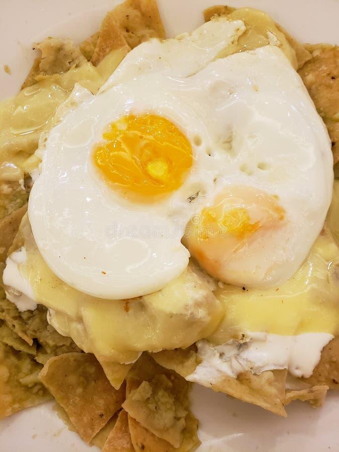 chilaquiles verts avec du fromage et les oeufs au plat fondus, nourriture mexicaine typique photos libres de droits