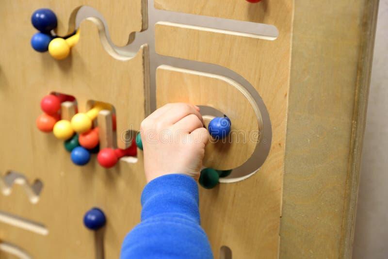 Child& x27 παιχνίδια χεριών του s με τον ξύλινο γρίφο στοκ εικόνες