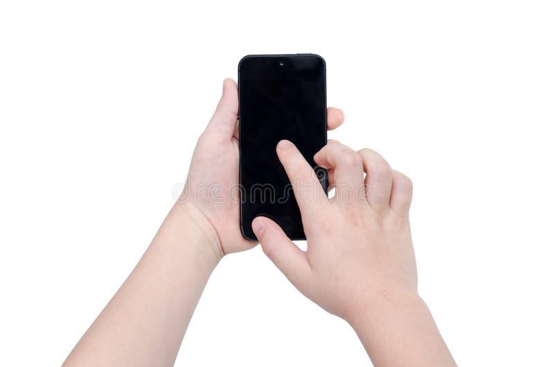 Child& x27; 拿着在白色的s手巧妙的电话 库存图片