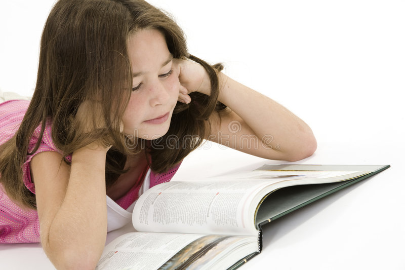 Child. Laying on a white background and reading a book stock images