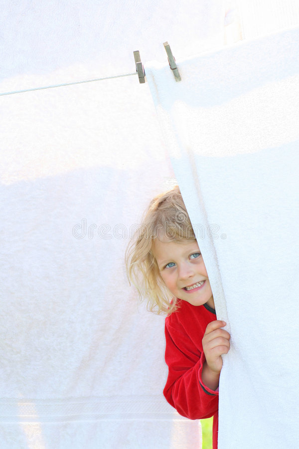 Child. A happy and smiling girl hiding behind a towel that is hanging on the clothesline outdoors royalty free stock photos