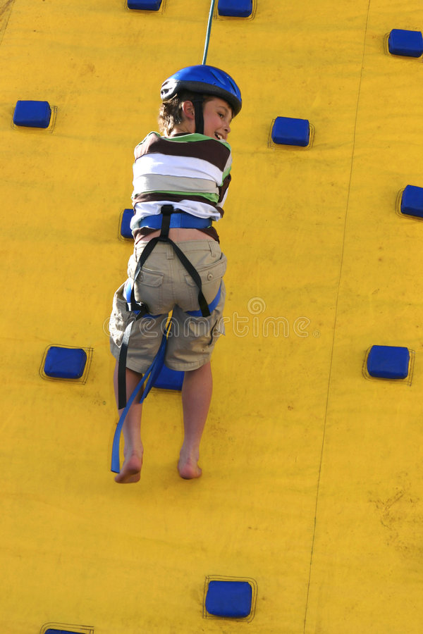 A child abseilling down a climbing wall stock image
