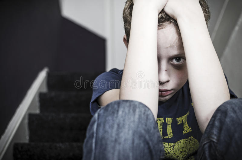 Child abuse. Sad boy sitting at home on stairs depressed and feeling miserable. Child neglecting or abuse. offender