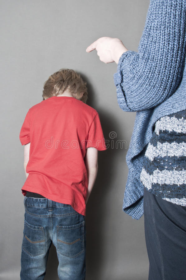 Child abuse. Scared child being told off by his violent mother royalty free stock photography
