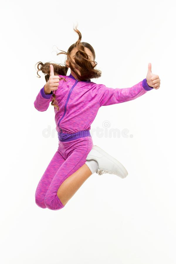 This child is active. Active little girl gesturing thumbs ups in motion isolated on white. Small child jumping in active. Sportswear. Fit and energetic kid royalty free stock images