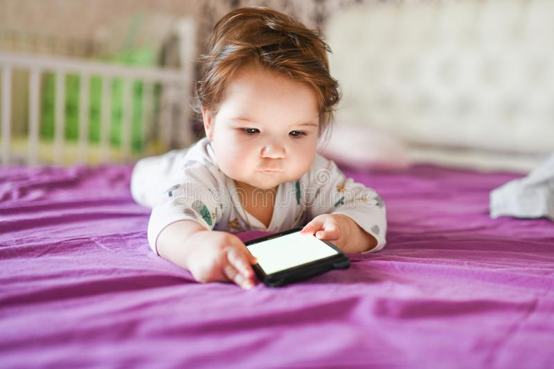 Child addiction to phones. radiation from the phone to the child. A little boy 0-1 years old with a smartphone in his hands looks stock photo