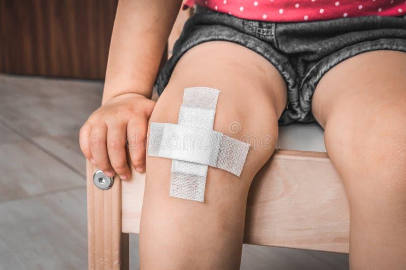 Child with adhesive bandage on knee. Injury concept royalty free stock photo