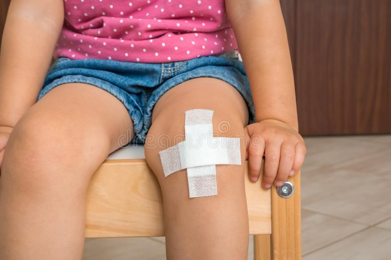 Child with adhesive bandage on knee. Injury concept royalty free stock images