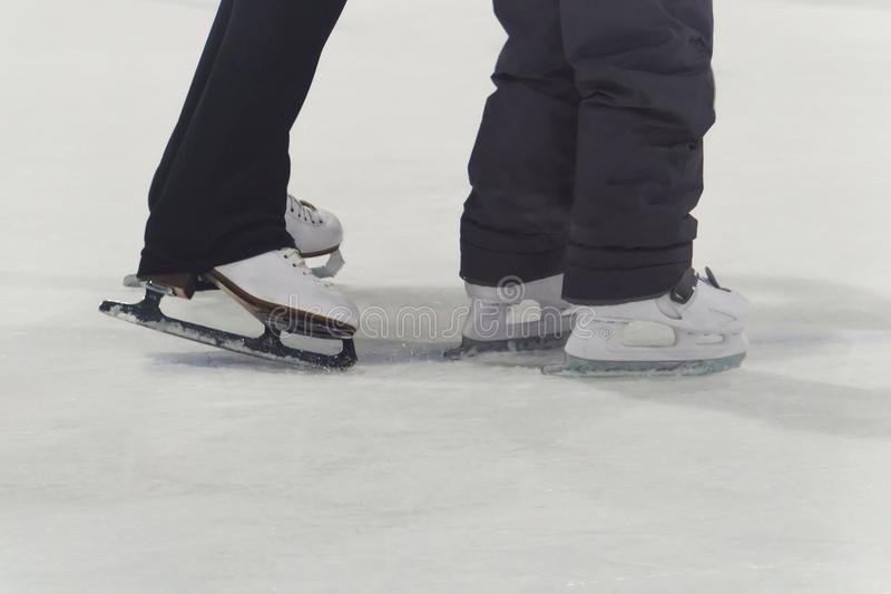child and adult skates at the ice rink stock photos