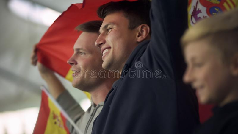 Child and adult Spanish football fans waving flag, singing national anthem. Stock photo stock images