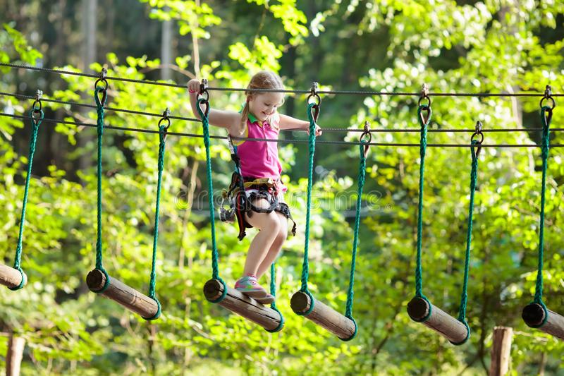 Child in adventure park. Kids climbing rope trail. Child in forest adventure park. Kids climb on high rope trail. Agility and climbing outdoor amusement center royalty free stock photo