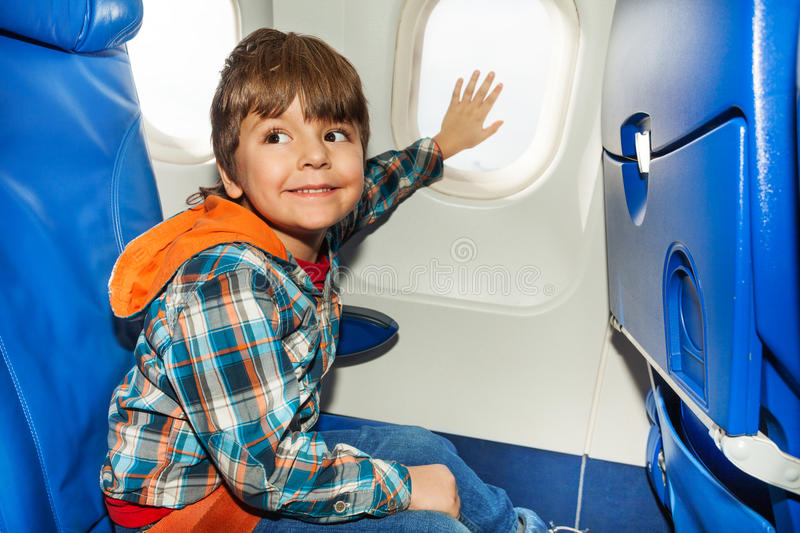 Child on airplane touch window with hand royalty free stock photos