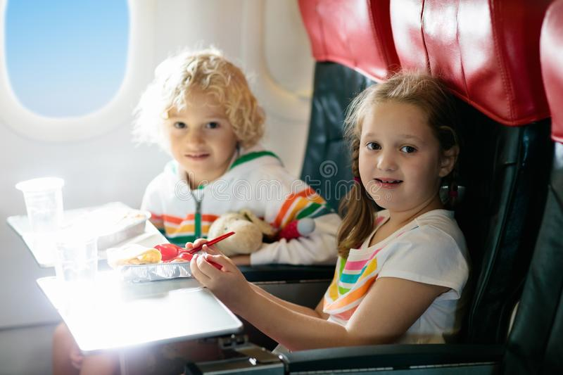 Child in airplane window seat. Kids flight meal. Children fly. Special inflight menu, food and drink for baby and kid. Girl and stock images