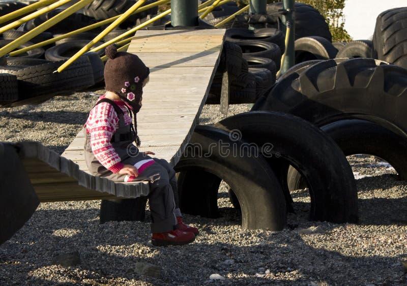 Child alone. Child sitting alone on a playground swing stock image