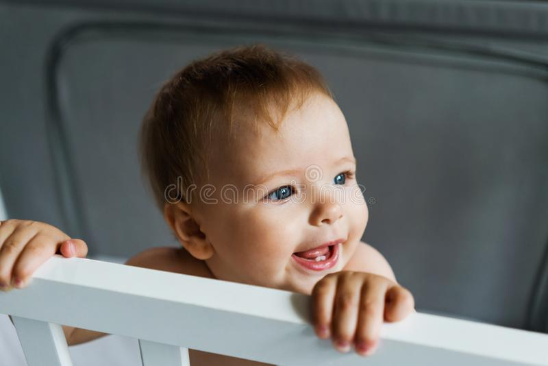 The child is in the crib. Close-up portrait of a nine-month-old smiling baby girl standing in the playpen. Cheerful happy child. A child alone stands at home in royalty free stock photo