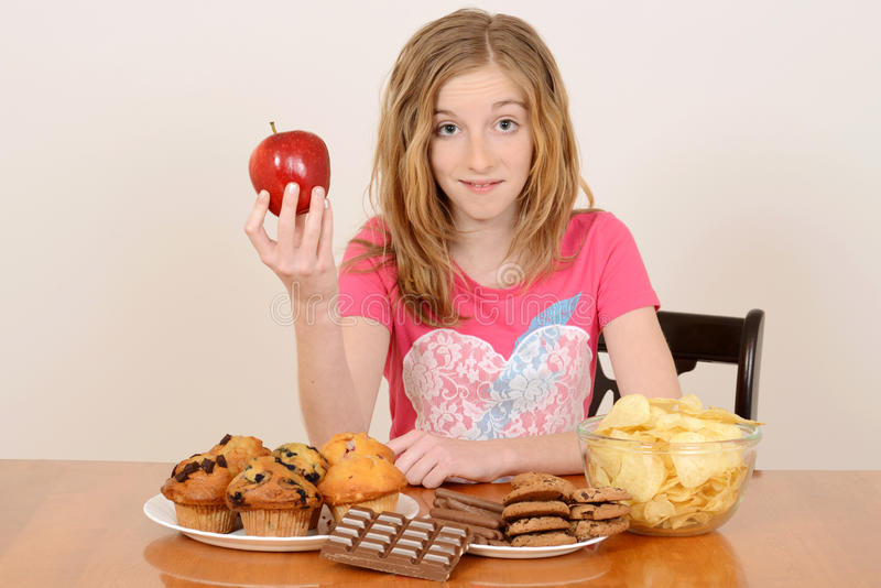 Child with apple and junk food concept stock images