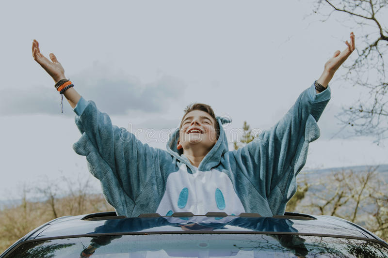 Child with arms aloft in the car. Window stock photo