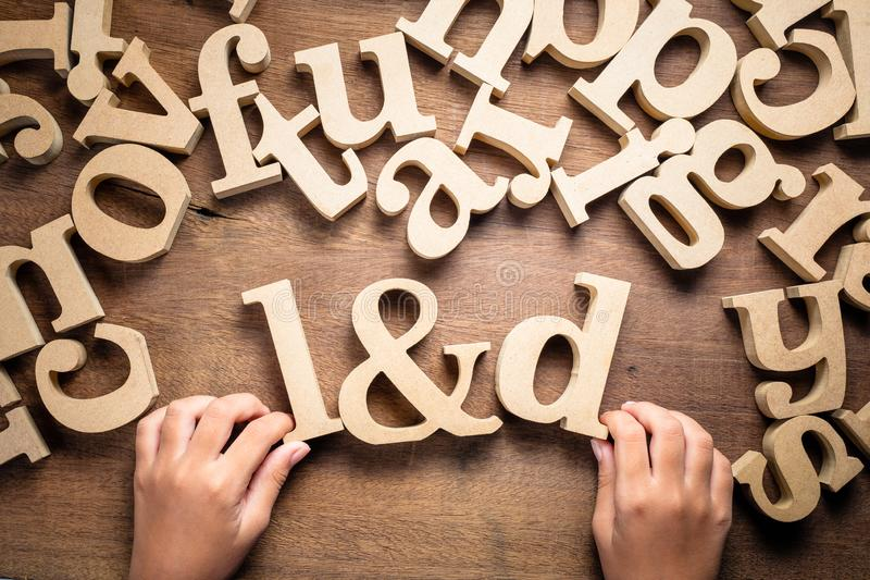 Child Arrange Alphabets as L&D Learning and Development. Closeup child`s hand arrange wooden alphabets on the table as L&D abbreaviation, Learning and royalty free stock photo
