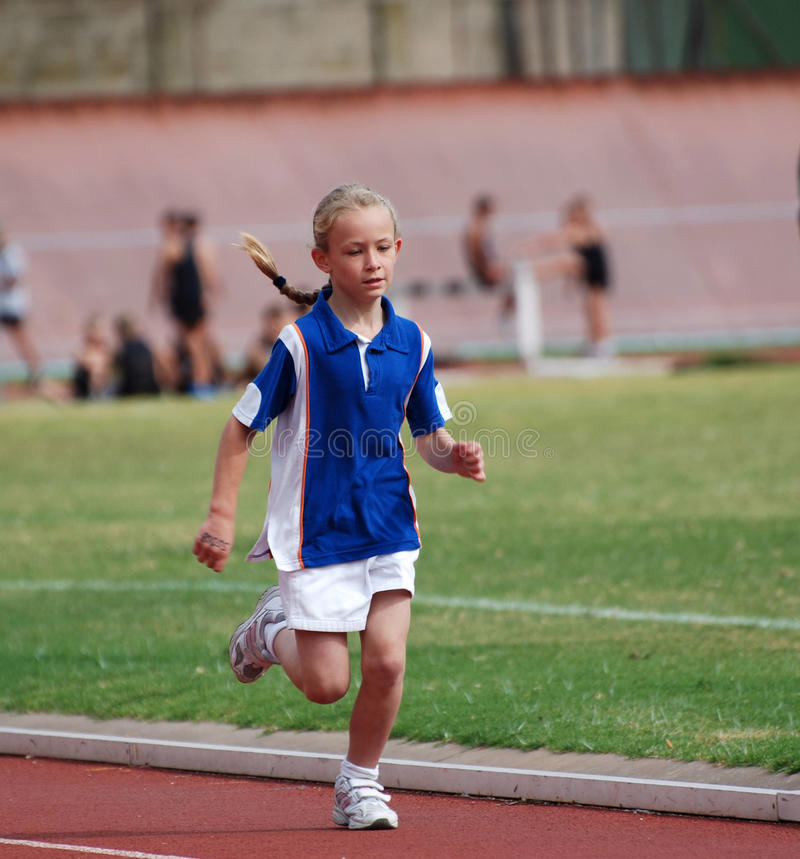 Child athlete running. A cute little Caucasian girl child athlete running a long distance on the track of the stadium outdoors royalty free stock image