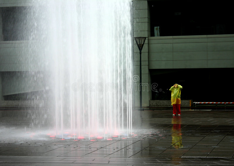 Child in Awe. A child is amazed by an interesting waterfountain stock images