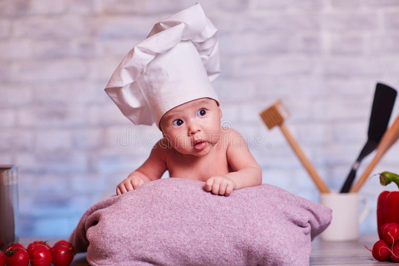 Child, baby girl lies on the kitchen table in a chef`s cap - next to him are vegetables, bell pepper, radish, broccoli, proper royalty free stock photo